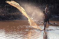Cambodian boys net fishing on the Tonle Sap Lake, an estuary of the Mekong River near Siem Reap.