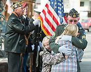 PRICE CHAMBERS/JACKSON HOLE DAILY<br /> Josie Campbell, 10, and Sarah Bentlage, 12, hug American Legion Post No. 43 Commander David Bentlage before the Veterans Day ceremony on the Town Square on Friday morning.