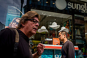 Male consumers walk past a sunglasses shop featuring three hats suspended from the store window ceiling. The three white hats symbolise a London summer, hanging in clear space above the mens' heads - one, as if perched on top of one male's thinning hair. It is a scene of gender and mysogeny.