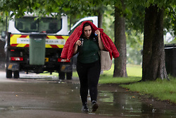 © Licensed to London News Pictures. 07/08/2021. London, UK. A woman uses her coat to shelter from rain in Greenwich Park in South East London. A yellow weather warning for thunderstorms is in place for parts of England. Photo credit: George Cracknell Wright/LNP