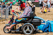 A lady in a mobility scooter gets into teh festival spirit as Black Honey play the Obelisk Arena - The 2018 Latitude Festival, Henham Park. Suffolk 15 July 2018