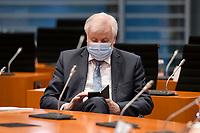 02 DEZ 2020, BERLIN/GERMANY:<br /> Horst Seehofer, CSU, Budnesinnenminister, , mit Mund-Nase-Maske, tippt auf sein Smartphone, vor Beginn einer Kebinettsitzung, Internationaler Konferenzsaal, Bundeskanzleramt<br /> IMAGE: 20201202-01-001<br /> KEYWORDS: Sitzung, Kabinett, Atemmaske, Maske, Corvid-19, Corona, Pandemie