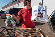05 NOVEMBER 2013 - PHOENIX, AZ: CODY SHUMWAY, a volunteer, puts food into a client's car at St. Mary's Food Bank in Phoenix, AZ. Demand at St. Mary's has continued to increase even as government assistance is reduced. Over the summer, St. Mary's Phoenix location provided emergency food for 300 - 400 families per day. They are currently supporting about 600 families per day. Part of the increase is seasonal but a large part of it is no clients coming to the food bank for the first time. More than 1.1 million Arizonans who use the Supplemental Nutrition Assistance Program, known as food stamps, saw their benefits reduced Friday, Nov. 1, in a long-planned national cut that was tied to the economic stimulus which was a part of the American Recovery and Reinvestment Act. The cuts imposed last week range from $11 a month for a single recipient to $65 or more for large families. Many of SNAP receipients already use food banks to supplement their government assistance and the cuts in the SNAP program are expected to increase demand even more.   PHOTO BY JACK KURTZ