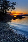 The sun sets over a notch in the rocky shoreline that borders Sunset Beach in Washington Park on Fidalgo Island, Anacortes, Washington. The sun's glint shines on the water of Rosario Strait. Blakely Island, one of the San Juan Islands, is visible in the background.