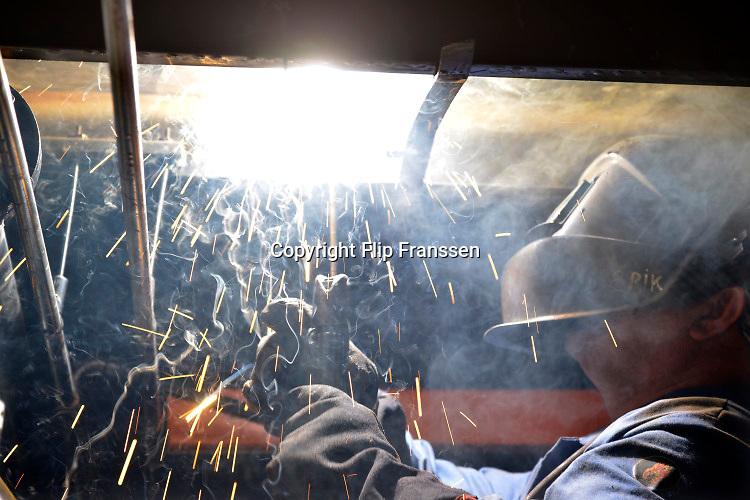 Nederland, Urk, 9-5-2017 Lasser aan het werk op een werf voor ombouw en onderhoud aan grote jachten en kleine vissersschepen. Hij is bezig met het lassen van de dekconstructie voor een nieuw schip. Foto: Flip Franssen