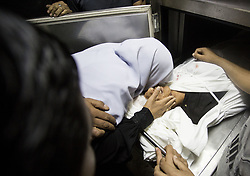 October 3, 2018 - Gaza City, The Gaza Strip, Palestine - The family of Ahmed Abu Hubal, 15, who was killed during clashes with Israeli forces near the Erez border crossing with Israel, is carrying his head as he looks at his body in a morgue in a hospital in Beit Lahia in the north. Gaza Strip, October 3, 2018. - Abu Habil, a spokesman for the Ministry of Health in the Gaza Strip, died of wounds to the head after being hit by a tear gas fired by soldiers near a checkpoint between Israel and the Gaza Strip. Gaza strip. The Israeli army did not immediately respond to a request for comment. (Credit Image: © Mahmoud Issa/Quds Net News via ZUMA Wire)