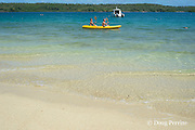 guests paddling a kayak past moored sportfishing boat, in Hunga Lagoon, off Ika Lahi Lodge, Hunga Island, Vava'u, Kingdom of Tonga, South Pacific