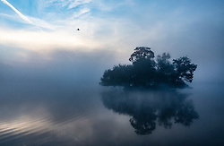 © Licensed to London News Pictures. 22/09/2021. London, UK. A misty start to the day at dawn on Pen Ponds in Richmond Park on the first day of autumn. Warm temperatures have heralded the start of the autumn season this week. Photo credit: Peter Macdiarmid/LNP