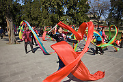 Women practise tai chi dancing with ribbons in park of the Temple of Heaven, Beijing, China
