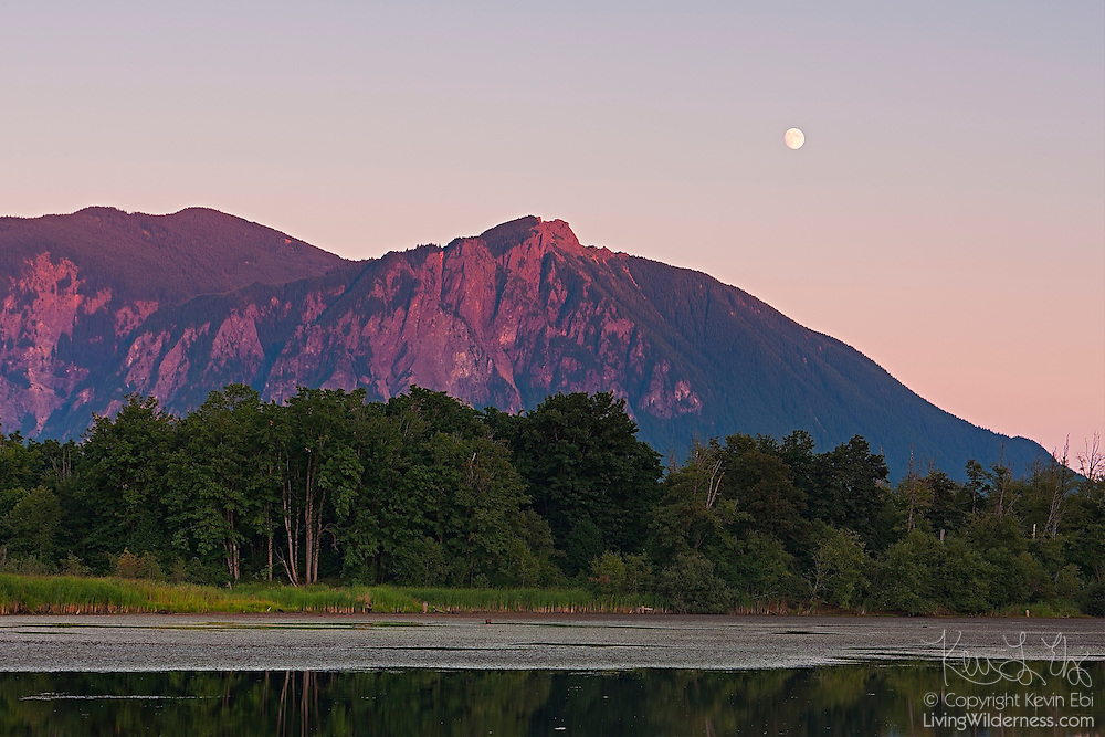 The nearly full moon rises over Mount Si, a 4,167 foot (1,270 meter) mountain located near North Bend, Washington. Mount Si is a remnant of an oceanic plate volcano. Its summit is a class 3 rock scramble known as the Haystack.