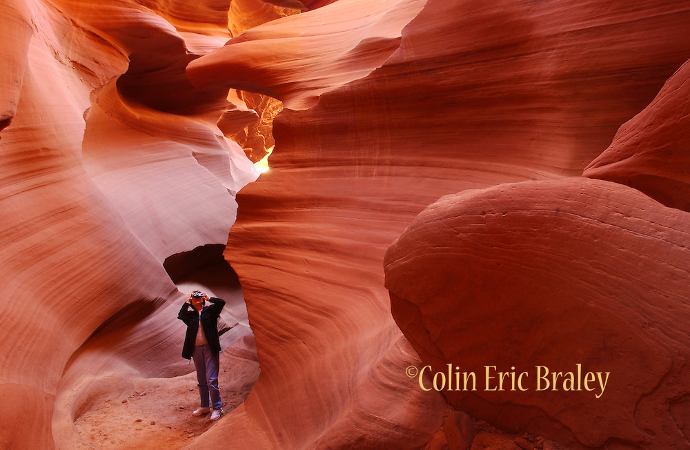 """An unidentified tourist takes a photograph deep inside Lower Antelope Canyon. The """"lower"""" slot canyon is less traveled than it's sister, Upper Antelope Canyon, but it provides those who visit many unique images. Both are located on Navajo lands near Page, Arizona."""