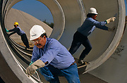 "Precast concrete pipes are prepared for distribution by a Mexican-born employees at Hanson Pipe & Products, Grand Prairie, Texas, USA. They are inspcting the inner-surfaces and tongue and groove seals of the horizontal pipes wearing obligatory hard hats and corporate blue shirts. Precast concrete is made from a reusable mold or ""form"" and cured in a controlled environment, then transported to the construction site and lifted into place. Used in the construction of commercial building components, bridges, manholes and retaining walls, these products are the strongest pipe available, designed and plant tested to resist any load required with a design life of 70-100 years."