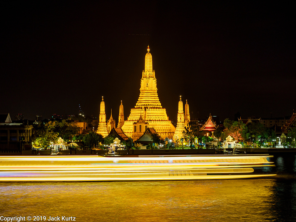 """06 MARCH 2019 - BANGKOK, THAILAND:  Boat traffic on the Chao Phraya River goes past Wat Arun just after sunset. Wat Arun Ratchawararam Ratchawaramahawihan or Wat Arun (""""Temple of Dawn"""") is a Buddhist temple (wat) in Bangkok on the Thonburi side of the Chao Phraya River. The temple derives its name from the Hindu god Aruna, who is personified as the rising sun. Wat Arun is among the best known of Thailand's temples. The temple has existed since at least the seventeenth century, but its distinctive prang (spires) were built in the Khmer style in the early nineteenth century during the reign of King Rama II.  PHOTO BY JACK KURTZ"""