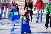 03 JANUARY 2021 - DES MOINES, IOWA: A child wearing a bison hat for warmth holds onto a skating trainer while on the ice at Brenton Skating Plaza in downtown Des Moines. The ice skating rink usually opens in late November and stays open through late February or March, depending on weather. Covid restrictions limited capacity to less than half, skaters were encouraged to social distance, and skaters were required to wear proper face masks. This year the rink was forced to close January 3, after only six weeks, because it wasn't possible to comply with COVID-19 restrictions and still be profitable. Restrictions caused by the Coronavirus pandemic have limited many public events this winter in Iowa.    PHOTO BY JACK KURTZ
