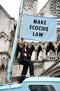 Extinction Rebellion supporters park a blue boat, named the Polly Higgins in memory of the lawyer who fought for ecocide to be made a crime in front of the Royal Courts of Justice on the Strand on July 15th 2019 in London, United Kingdom. Last week it was announced that over 1000 activists who were arrested in the April protests face prosecution. Musician Jess Winter performs on the boat for the activists.