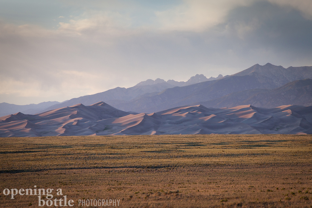 Sunset over Great Sand Dunes National Park and Preserve with the 14,000-foot peaks of the Sangre de Cristo Mountains in the distance, including Crestone Peak, Crestone Needle and Kit Carson Peak.