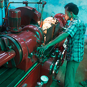 CAPTION: Operating the lathe, powered by energy derived from biomass by DESI Power. LOCATION: Gayari, Araria District, Bihar, India. INDIVIDUAL(S) PHOTOGRAPHED: Mujaheed.