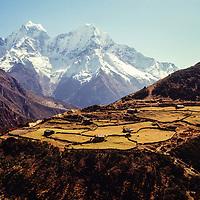 A Sherpa farming village in Nepal's Gokyo Valley is dwarfed by the Himalayan peaks 22,250-foot Kangtega (L) and 21,730-foot Thamserku.