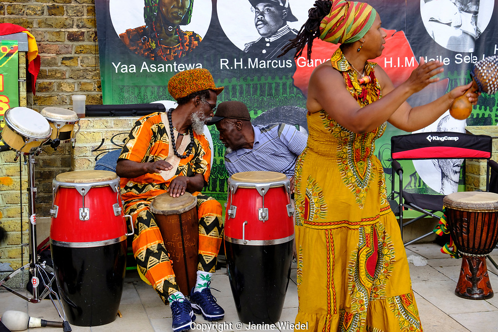 Rastafarian musicians chatting and  playing Groundation drumming and reggae music at annual Reparation Rebellion event on Afrikan Emancipation Day in Windrush Square Brixton 2021.