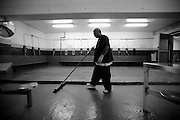 Quinones Edwin sweeps the recreation room where inmates work out or make phone calls.  The Bristol County Jail & House of Correction located on Ash Street in New Bedford, Massachusetts was started in 1829, and is the oldest running jail in the United States.   The Ash street jail, as it is known, has been a controversial facility since it opened.  It is believed to be the site of the last pubic hanging in Massachusetts sometime in the 1890's.  Two big riots broke out in the 90's (1993, 1998) and since then the facility has been modified to alleviate some of the crowded conditions that resulted in the riots.