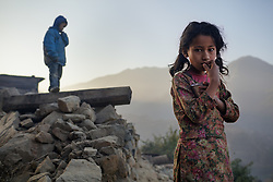 Sushil, 7, and his sister Sumitra, 10, wait for their parents to come down from the cow shed before they can have breakfast and get ready for school. The couple did not come to their temporary village home the previous night, leaving their front door locked. When this occasionally happens, the kids eat and spend the night with neighbors. The rubble and debris is left over from the earthquake.<br /> <br /> Niruta and Durga were married 9 years ago, when they were just 14 and 16 years old in the Kagati village of Nepal. The 2015 earthquakes devastated Nepal and left girls and women in an increasingly vulnerable position, leading experts to believe child marriage rates will increase over the coming years.