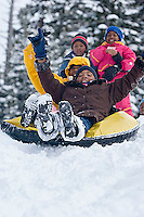 Young kids riding snowtube at Kirkwood ski resort near Lake Tahoe, CA.<br />