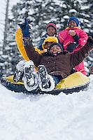 Young kids riding snowtube at Kirkwood ski resort near Lake Tahoe, CA.<br />