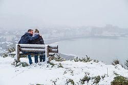 © Licensed to London News Pictures. 10/12/2017. Aberystwyth, UK. A couple embrace while watching the first snow of the winter at Aberystwyth on the Welsh coast, as the wintry conditions spread of much of the middle of the UK.  People are out  walking on Constitution Hill overlooking the town, making the most of the snowy scenes .Photo credit: Keith Morris/LNP