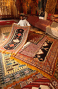 MOROCCO, TANGIER craft shop in the old city with merchants showing traditional Moroccan carpets for sale
