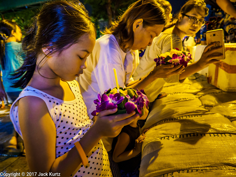 """03 NOVEMBER 2017 - BANGKOK, THAILAND:  A woman uses her smart phone to photograph her daughter praying with her krathong during Loi Krathong near Wat Prayurawongsawat on the Thonburi side of the Chao Phraya River. Loi Krathong is translated as """"to float (Loi) a basket (Krathong)"""", and comes from the tradition of making krathong or buoyant, decorated baskets, which are then floated on a river to make merit. On the night of the full moon of the 12th lunar month (usually November), Thais launch their krathong on a river, canal or a pond, making a wish as they do so. Loi Krathong is also celebrated in other Theravada Buddhist countries like Myanmar, where it is called the Tazaungdaing Festival, and Cambodia, where it is called Bon Om Tuk.    PHOTO BY JACK KURTZ"""