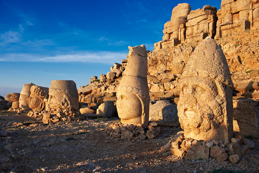 Pictures of the statues of around the tomb of Commagene King Antochus 1 on the top of Mount Nemrut, Turkey. Stock photos & Photo art prints. In 62 BC, King Antiochus I Theos of Commagene built on the mountain top a tomb-sanctuary flanked by huge statues (8–9 m/26–30 ft high) of himself, two lions, two eagles and various Greek, Armenian, and Iranian gods. The photos show the broken statues on the  2,134m (7,001ft)  mountain. 1 .<br /> <br /> If you prefer to buy from our ALAMY PHOTO LIBRARY  Collection visit : https://www.alamy.com/portfolio/paul-williams-funkystock/nemrutdagiancientstatues-turkey.html<br /> <br /> Visit our CLASSICAL WORLD HISTORIC SITES PHOTO COLLECTIONS for more photos to download or buy as wall art prints https://funkystock.photoshelter.com/gallery-collection/Classical-Era-Historic-Sites-Archaeological-Sites-Pictures-Images/C0000g4bSGiDL9rw