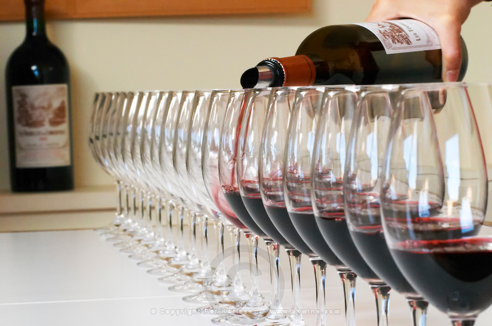A straight row of glasses lined up for tasting being filled up with red wine - Chateau Baron Pichon Longueville, Pauillac, Medoc, Bordeaux, Grand Cru