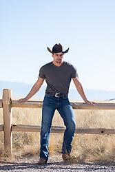 sexy cowboy leaning against a rustic fence
