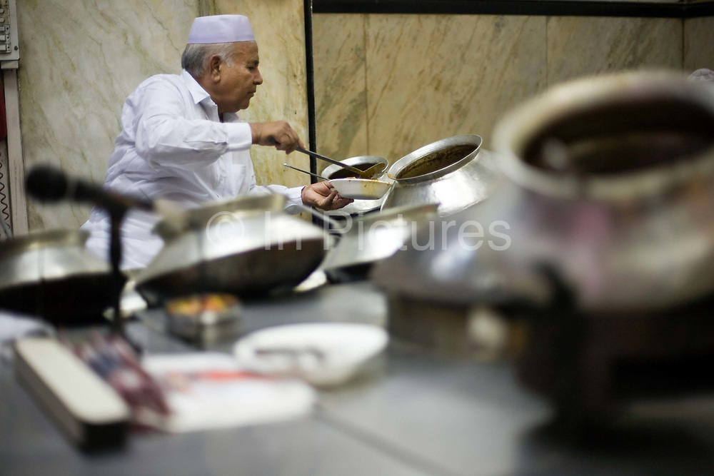 Salahuddin, one of the directors at Karim's Restaurant serves food from pots. Delhi, India<br /> Karim's is a Delhi landmark was started by Haji Karimuddin who decided to open a restuarant catering to people coming to Delhi for the Coronation Durbar in 1911