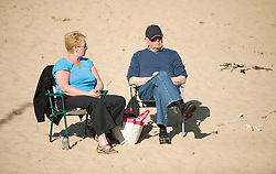 © Licensed to London News Pictures. 28/03/2012..Saltburn, England..As temperatures rise this week the beach at Saltburn in Cleveland attracts the visitors as they enjoy the warm weather. A couple relax in the morning sunshine...Photo credit : Ian Forsyth/LNP