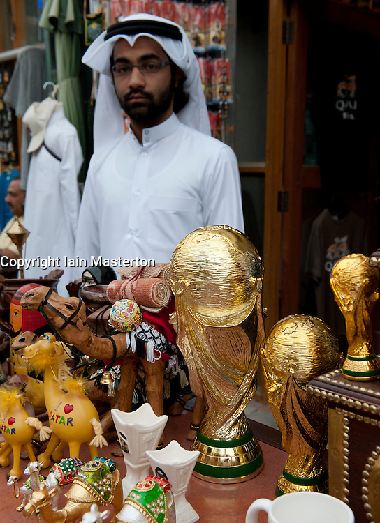 Trader selling replica World Cup trophy on market stall in Souq Waqif in Doha Qatar