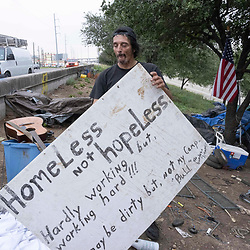 Musician and handyman Douglas Crawford holds a sign in his camp at the corner of Ben White Blvd. and south Congress Avenue in Austin, TX where he's lived for over a year. Crawford, 60, says he stays to himself and isn't worried about Austin's new homeless crackdown and camping ban starting Tuesday.