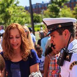 Baltimore, MD, USA - June 16, 2012: A Mexican Naval Officer speaks with a tourist at the Inner Harbor in the City of Baltimore, Maryland.