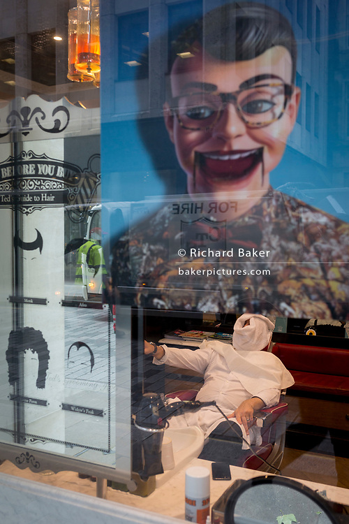 A businessman has a hot towel treatment a barber's chair in the grooming room at the rear of clothing retailer, Ted Baker London, on 14th September 2017, in the City of London, England.