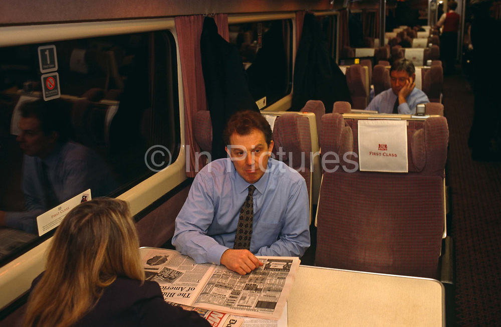The Rt. Hon. Tony Blair MP, as Leader of the Opposition, stares in deep thought whilst on a train en-route to an evening Labour Party rally in Nottingham, 2 years before his victory in the 1997 General Election that eventually made him British Prime Minister. Blair is with an unknown Downing Street assistant and is has been reading the London Evening Standard newspaper in the First Class carriage at a time when fellow-passengers take little notice of the future controversial world statesman. Then, he could travel in relative obscurity, without large security details. Blair is wearing a blue shirt with a sober, patterned tie and his hair is still dark without the greyness that would appear rapidly when the pressures of office prematurely aged him. It is dark outside and we see no detail through the window of the vast Victorian mainline station outside.