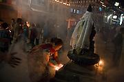 A woman prays and lights butter lamps in ritual offering during Buddha Jayanti (Buddha's birthday) at Boudhanath Stupa, Kathmandu, Nepal on May 9, 2009.