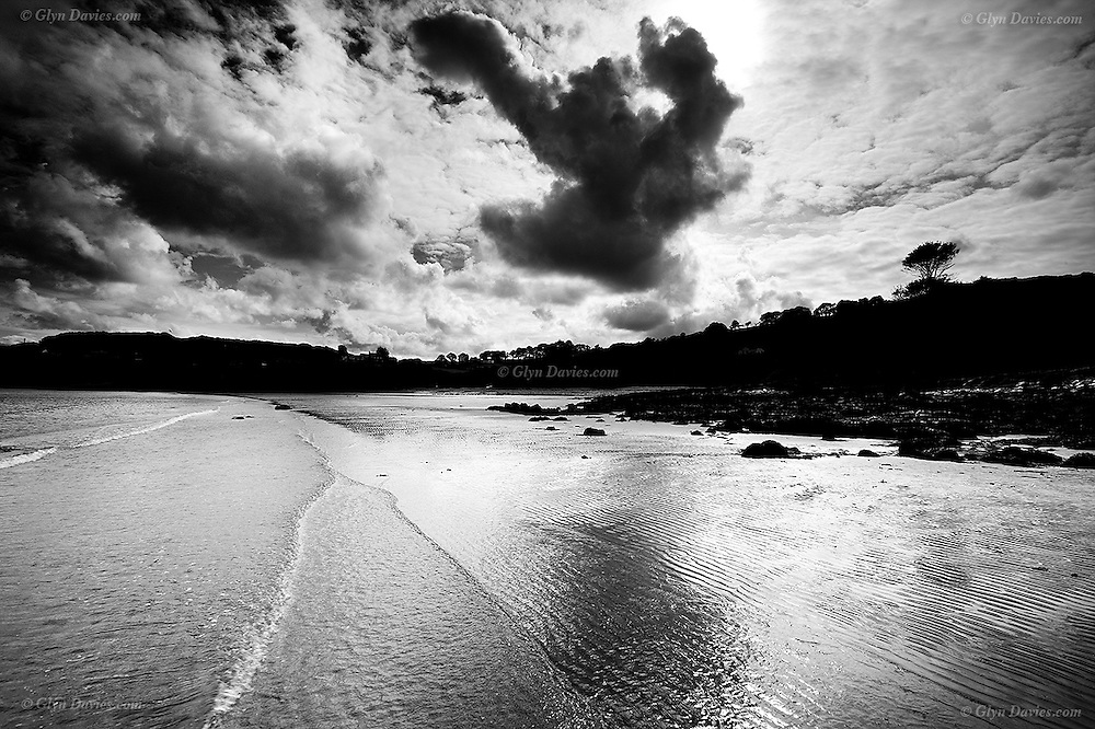Morning light over tiny waves in showery weather at Traeth Bychan beach, East Anglesey. A cloud shaped like a jumping figure hangs in the sky.