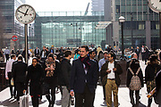 A British male city workers stands in Reuters Plaza while many other people walk around him in Canary Wharf financial district London, England, United Kingdom.