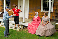 Old Bethpage, New York, U.S. 31st August 2013. PATRICIA JOSEPH, of College Point, in red dress, and JANE HEILIG, of Bethpage, in taupe dress, are talking with a man and woman visiting during the Olde Time Music Weekend at Old Bethpage Village Restoration, where popular music of the Civil War period is performed, and visitors learn traditional 1800's contradances. Joseph and Helig, who are wearing American Civil War era style clothing and are members of the Old Bethpage Village Dancers, are sitting on the porch of 12 Lawrence House, which originally was located across the street from the home Joseph was born in.