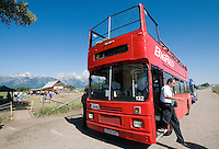 BRADLY J. BONER / NEWS&GUIDE <br /> The double-decker, open-top Big Red Tours bus delivers riders to the 100th anniversary celebration of the Moulton Barn on Saturday in Grand Teton National Park. Owners Redeem Sumicad and McNeil Watson hope to soon use the bus for historic tours of Jackson and private functions.