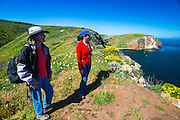 Hikers watching for whales at Scorpion Cove, Santa Cruz Island, Channel Islands National Park, California USA