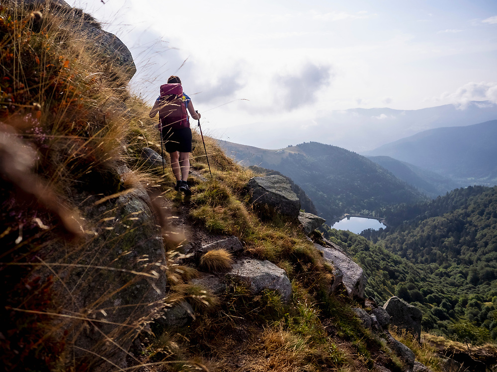 Rear view of women hiking towards Vosges mountain and lake Schiessrothried seen in backgrounds at Lac Blanc, France