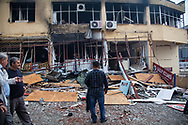 Residents of Reyhanli and shop owners and workers stand outside their stores and survey the damage to the buildings after a double car bombing in Reyhanli, a Turkish border town with Syria.