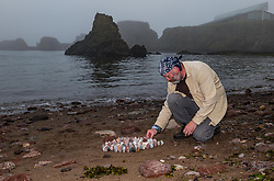 Dunbar, East Lothian, Scotland, UK, 9th July 2021. European Stone Stacking Championship: Competitors who have arrived for the weekend championship practise their skills on the beach on a very misty day. The event, which was cancelled last year, is part of the Edinburgh Science Festival. There will be several challenges including the most stones stacked in 20 minutes, the best balance from a given set of stones and an artistic challenge, as well as a children's event. This year, there is also an online part to the competition. Pictured: one of the competitors, James Brunt, from Yorkshire, England, specialises in land art using standing stones.<br /> Sally Anderson | EdinburghElitemedia.co.uk