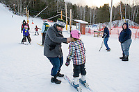 Jennifer Gagne helps her daughter Elizabeth with her helmet as she heads out for her weekly lesson with Becky Bartlett at the Abenaki Ski Area in Wolfeboro.  (Karen Bobotas/for the Laconia Daily Sun)